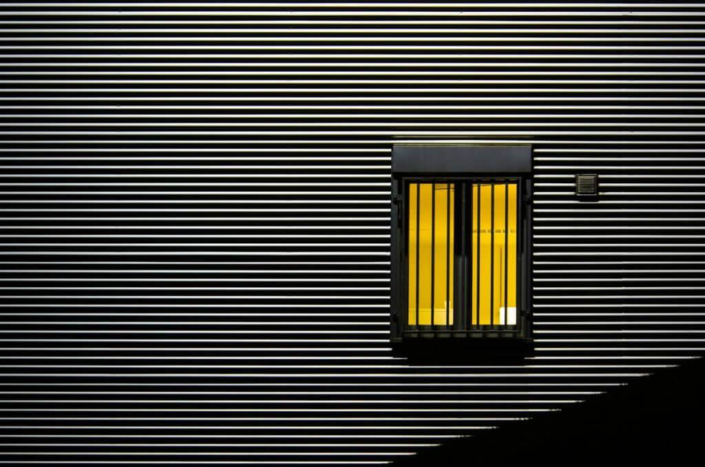 abstrakte Industriefassade mit beleuchtetem Fenster