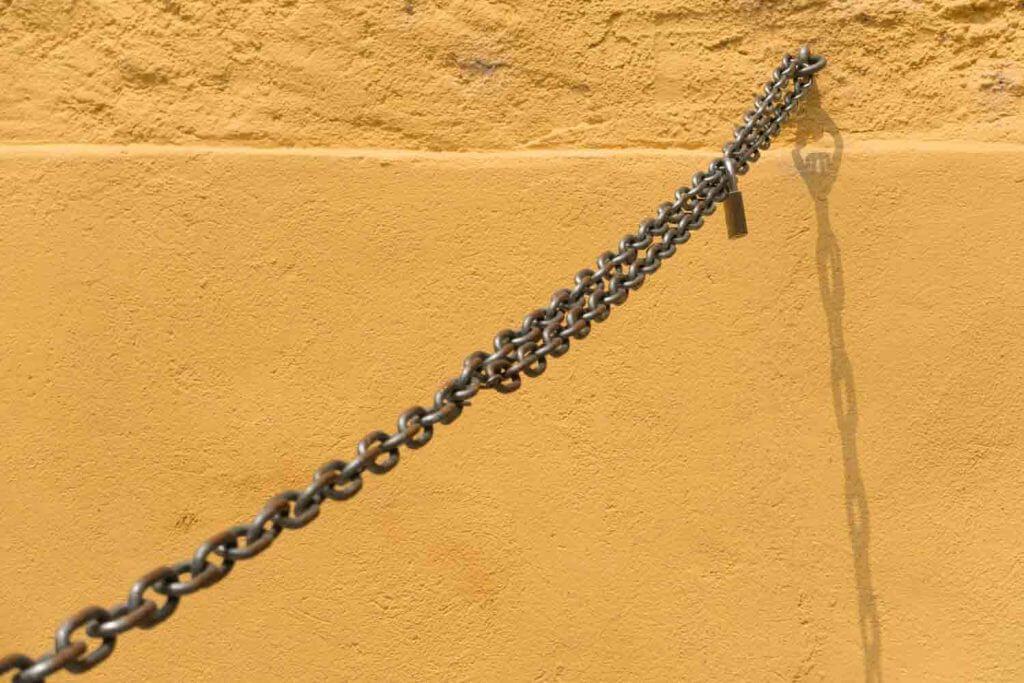 Kette an oranger Mauer in der Altstadt von Locarno - Monochrome Farben