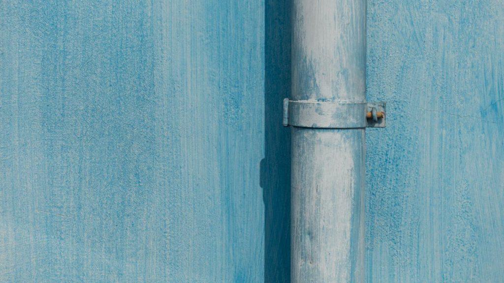 Regenwasserrohr an hellblauer Fassade